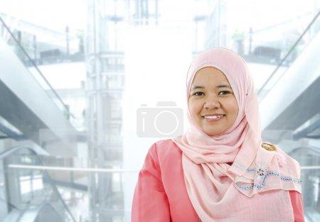Photo pour Asiatique musulmane debout sur fond de bureau moderne - image libre de droit