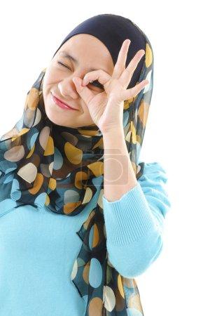 Photo pour Jeune femme musulmane concentrée par trou de la main - image libre de droit