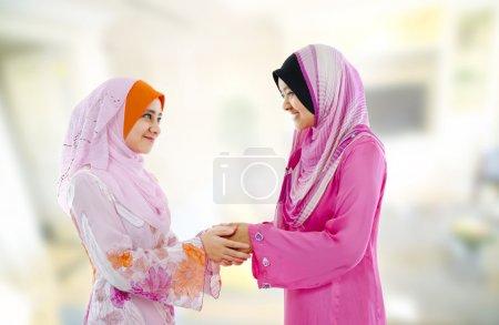 Photo pour Femme musulmane en vêtements traditionnels saluant les uns les autres, intérieur . - image libre de droit