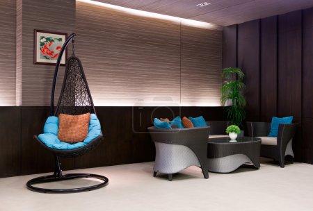 Photo pour Fauteuil suspendu à une chaîne dans le canapé de Hall d'hôtel avec oreillers bleus - image libre de droit