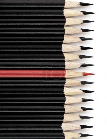 Foto de Fila de lápices negros con un lápiz rojo en el medio. Sobre fondo blanco con sombra - Imagen libre de derechos