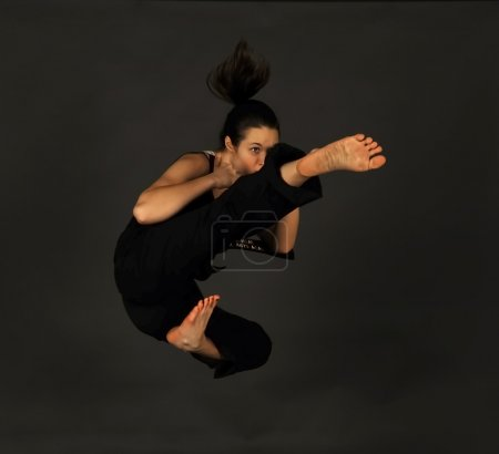 Photo for MMA - Female mixed martial arts warrior kicking on a black background. - Royalty Free Image