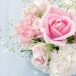 Huge bunch of pink and white roses over blue backg...