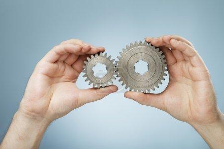 Photo pour Homme tenant dans ses mains deux roues dentées métalliques de tailles différentes . - image libre de droit