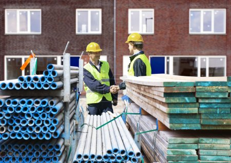 Photo pour Deux entrepreneurs en construction serrent la main derrière des piles de matériaux d'échafaudage, devant un complexe résidentiel nouvellement achevé - image libre de droit