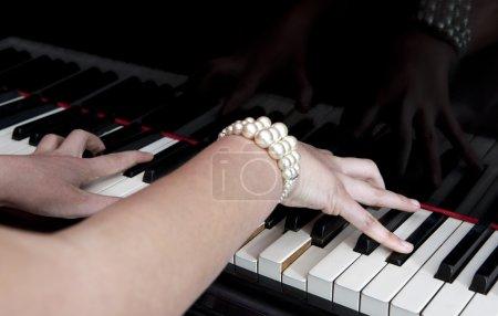 Photo pour Deux mains féminines jouant du piano à queue, se concentrant sur les doigts de la main droite de la femme . - image libre de droit