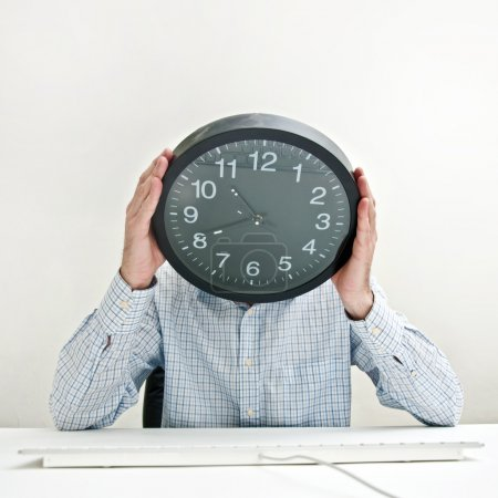 Desperate businessman with a clock instead of his ...