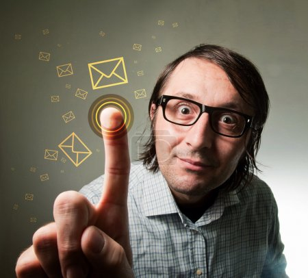 Photo for Nerd looking male using a touch screen to check his e-mail inbox, pressing an envelope representing an incoming e-mail message. Futuristic technology concept. - Royalty Free Image