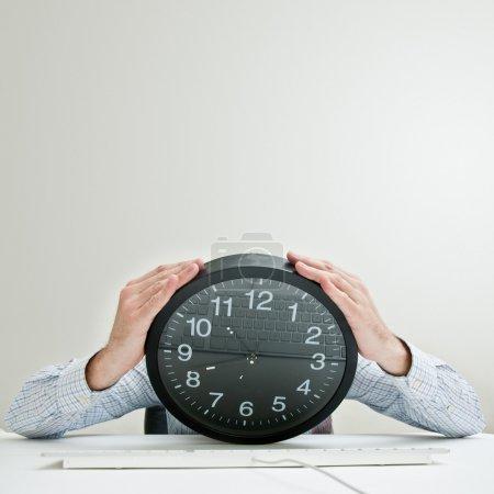 Photo pour Désespéré homme d'affaires avec une horloge au lieu de la tête, regardant désespérément vers le bas comme le temps passe. - image libre de droit