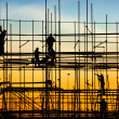 Construction site, silhouettes of workers against ...