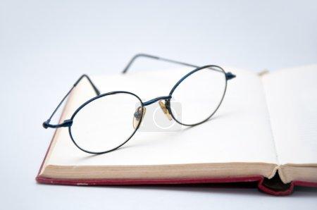 Photo pour Livre et lunettes symbolisant le concept de l'habitude de lire ou d'étudier - image libre de droit