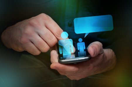 Photo for Man in black shirt is using his smartphone, close up image, focus on hands and the phone device. Computer generated icons representing contats in the address book. - Royalty Free Image