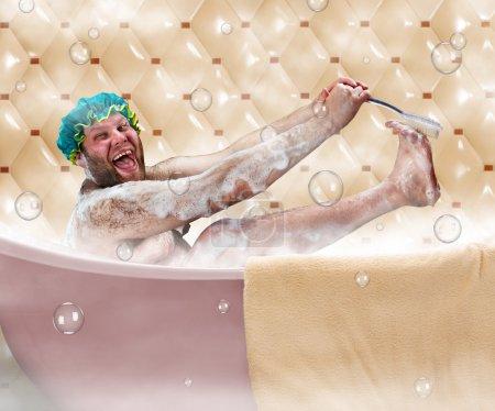 Photo pour Bizarre homme laid se laver la jambe dans un bain - image libre de droit