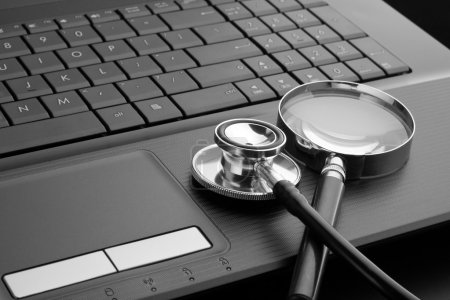 Stethoscope and magnifying glass on laptop