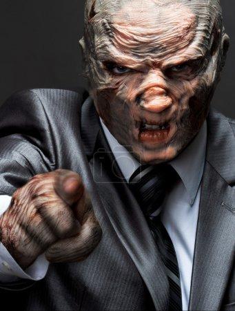 Foto de Monstruo furioso en traje de negocios apunta a - Imagen libre de derechos