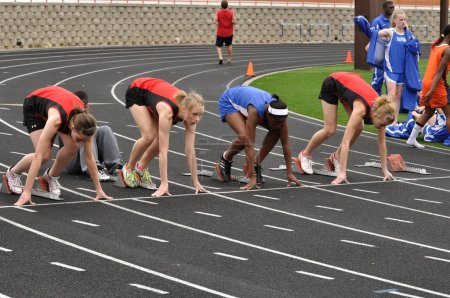Teen Girls in the Starting Blocks at a High School Sprint Race