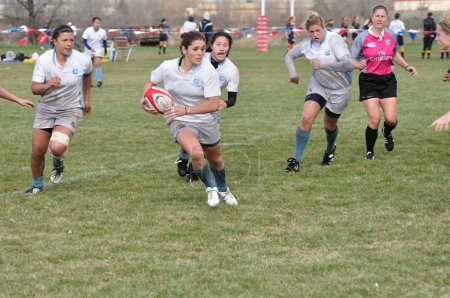 Player Running with the Ball in a Women's College Rugby Match