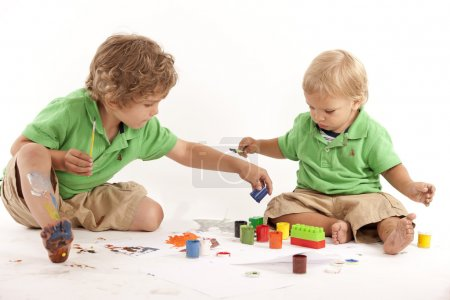 Siblings with paints and blocks