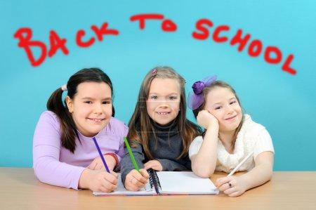 Happy school girls doing their work in classroom