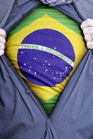 Photo for A Brazilian businessman rips open his shirt and shows how patriotic he is by revealing his countries flag beneath printed on a t-shirt - Royalty Free Image