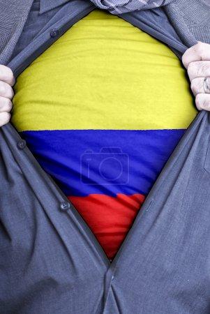 Photo pour Un homme d'affaires colombien déchire ouvert sa chemise et montre comment patriotique, il est en révélant que son pays drapeau sous imprimé sur un t-shirt - image libre de droit