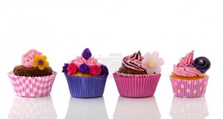 Photo pour Cupcakes rangée colorée avec des fleurs et de la crème de beurre rose - image libre de droit