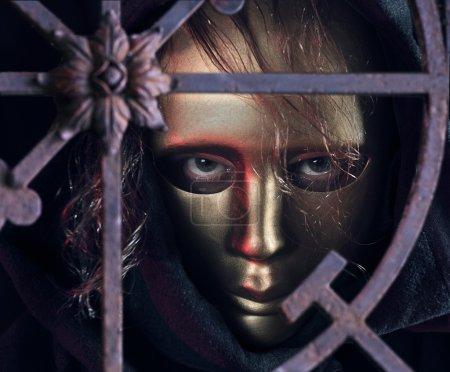 Foto de La persona con el pelo largo en una máscara de oro. - Imagen libre de derechos