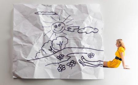 Photo pour La jeune femme en robe jaune et le dessin des enfants froissé . - image libre de droit