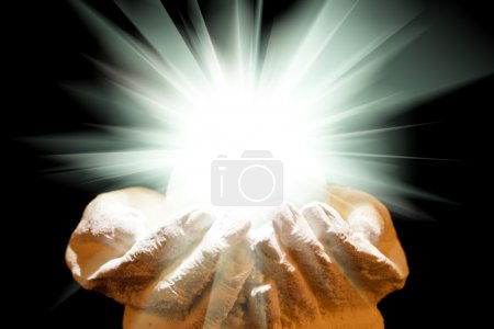 Spiritual light in cupped hands on a black background