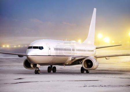 Photo pour Aéroport et avion blanc par temps non aérien, heure d'hiver - image libre de droit