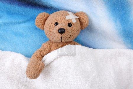 Foto de Oso de peluche con vendaje adhesivo sobre la cama. cerrar - Imagen libre de derechos