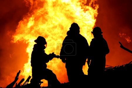 Three firemen fighting a raging fire with huge fla...