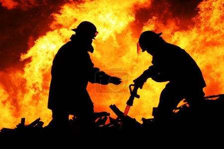 Silhouette of Firemen fighting a raging fire with ...