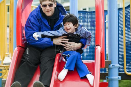Photo for Father going down slide with disabled son who has cerebral palsy - Royalty Free Image