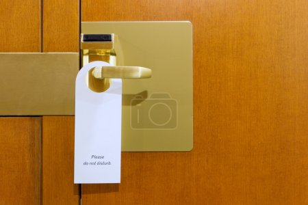 Do not disturb sign on brass and wood hotel room door