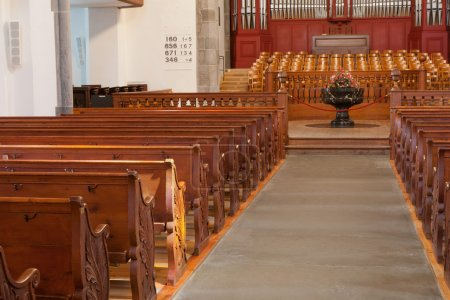 Rows of empty wooden church benches