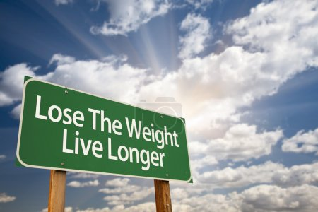 Photo for Lose The Weight Live Longer Green Road Sign with Dramatic Clouds, Sun Rays and Sky. - Royalty Free Image