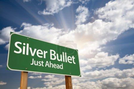 Photo pour Panneau de signalisation vert juste avant de balle argentée avec nuages dramatiques, les rayons de soleil et le ciel. - image libre de droit