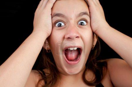 Photo pour Portrait d'une fille très surprise ou effrayée criant bruyamment avec ses mains sur sa tête isolée sur un fond noir - image libre de droit