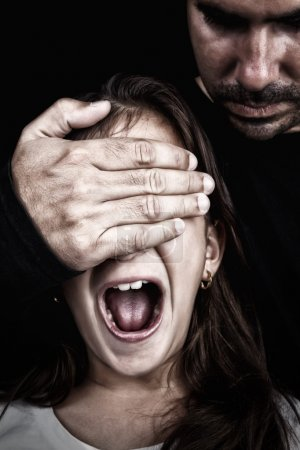 Child screaming while a man covers her eyes
