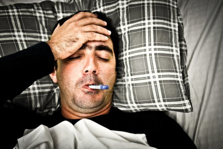 Photo for Dramatic desaturated image of a sick man laying in bed with fever - Royalty Free Image
