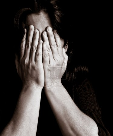 Photo for Desaturated portrait of a young woman crying and covering her eyes on a black background with space for text - Royalty Free Image