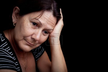 Photo for Portrait of a very sad and depressed older woman suffering from stress or a strong headache isolated on black - Royalty Free Image