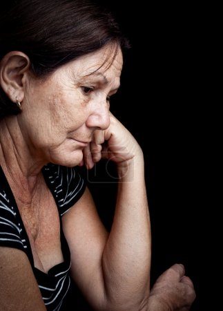 Photo for Portrait of a serious old woman with a worried expression isolated on black - Royalty Free Image