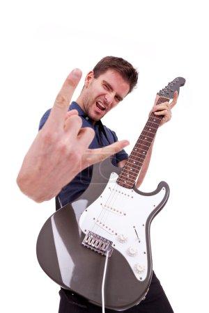 Photo pour Portrait d'une rockstar réussie tenant une guitare électrique sur fond blanc et amking un rock and roll à main geste - image libre de droit