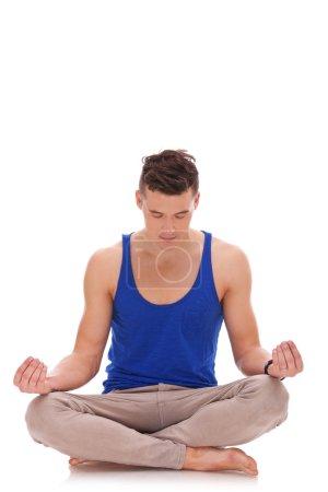 Handsome man meditating in lotus position