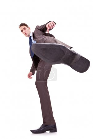 Photo for Young business man kicking something on white background. wide angle shot, view from bellow - Royalty Free Image