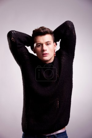 Photo for Fashion shot of a young handsome man in a sweater posing on gray background - Royalty Free Image