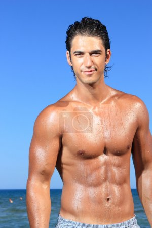 Sexy caucasian fit man posing in a beach...