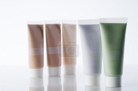 Photo pour De nombreux tubes cosmétiques avec des crèmes debout sur fond réfléchissant - image libre de droit